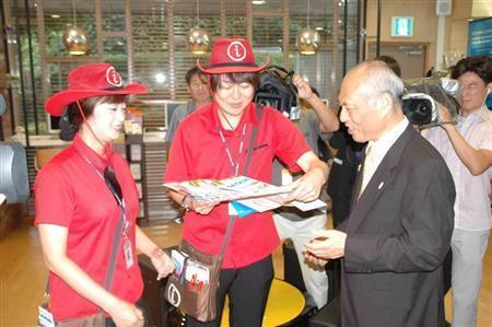 繁華街で外国人観光客対応に当たるボランティアにおすすめの店を尋ねる舛添要一知事(右)=7月24日、韓国・ソウル市の観光案内センター