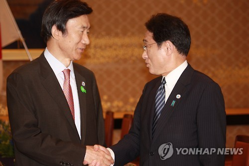 会談前に握手する尹氏(左)と岸田氏=21日、東京(聯合ニュース)