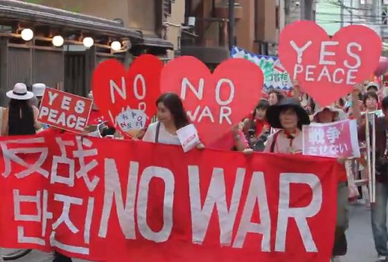 2015年7月19日に大阪市内で行われた「戦争反対! 愛と平和の女子パレ」の様子。支那語(簡体字)と朝鮮語(ハングル)と英語の横断幕