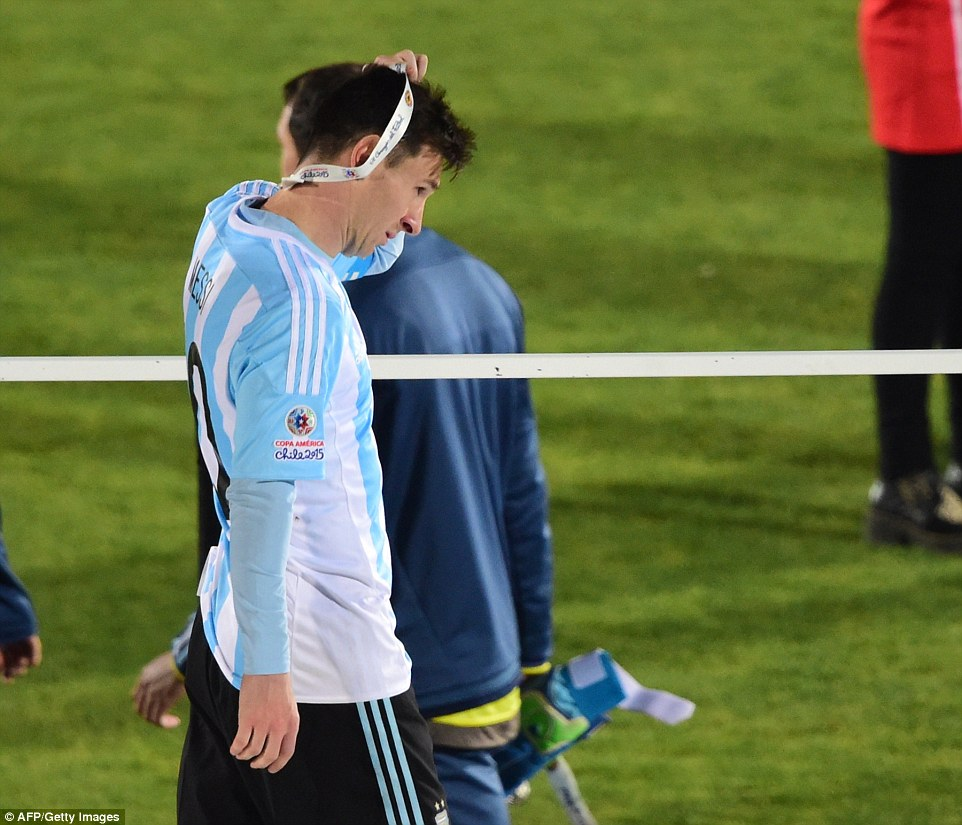 Lionel Messi takes his runners-up medal off