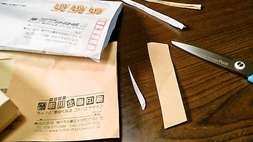 名刺の入った封筒をはさみで切る